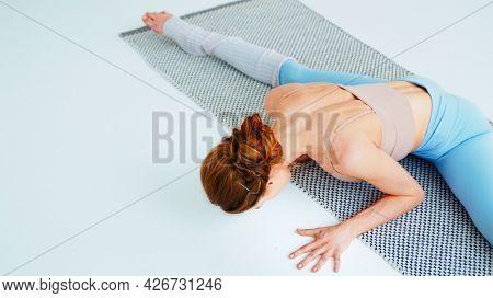 Young yoga coach doing gymnastics on a yoga mat