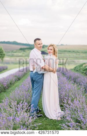 Lovely Middle Aged Couple Embracing At The Lavender Field. Love, People, Emotions And Lifestyle Outd