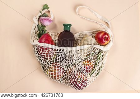 Cosmetic Eco Lotion And Red Fruits In Eco Bag On Beige Background. Sustainable Lifestyle. Eco-friend