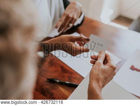 Woman handing a business card mockup