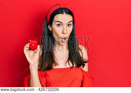 Young brunette woman holding engagement ring for proposal scared and amazed with open mouth for surprise, disbelief face