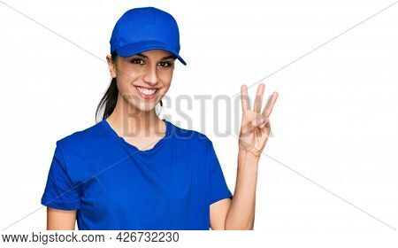 Young hispanic girl wearing delivery courier uniform showing and pointing up with fingers number three while smiling confident and happy.