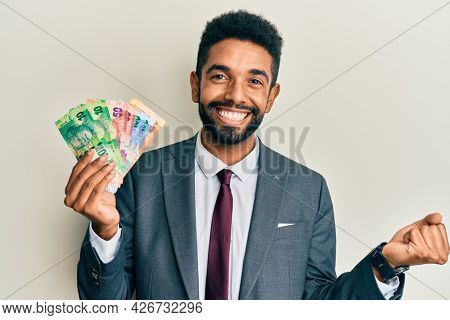 Handsome hispanic business man with beard holding south african rand banknotes screaming proud, celebrating victory and success very excited with raised arm