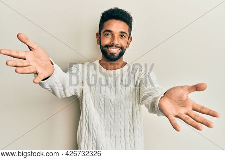 Handsome hispanic man with beard wearing casual winter sweater looking at the camera smiling with open arms for hug. cheerful expression embracing happiness.