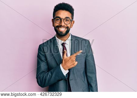 Handsome hispanic business man with beard wearing business suit and tie cheerful with a smile of face pointing with hand and finger up to the side with happy and natural expression on face