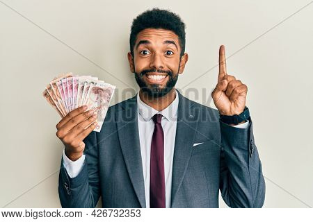 Handsome hispanic business man with beard holding turkish lira banknotes smiling with an idea or question pointing finger with happy face, number one