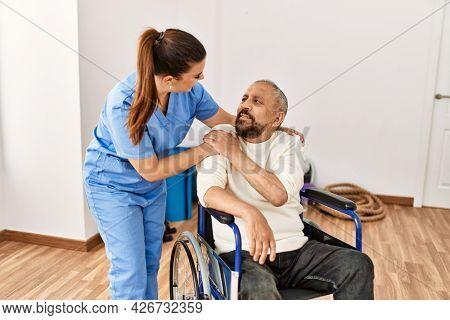 Senior man sitting on wheelchair and geriatric nurse at rehabilitation clinic