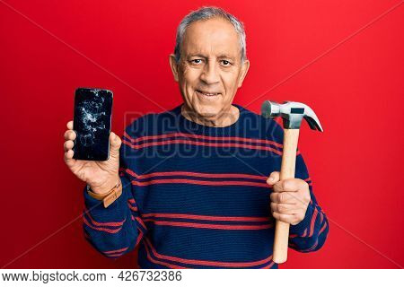 Senior hispanic man holding broken smartphone showing cracked screen and hammer smiling with a happy and cool smile on face. showing teeth.