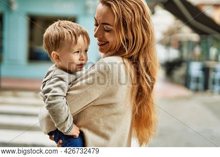 Beautiful family of mother and baby son hugging and bonding together with love. Parent and toddler outdoors