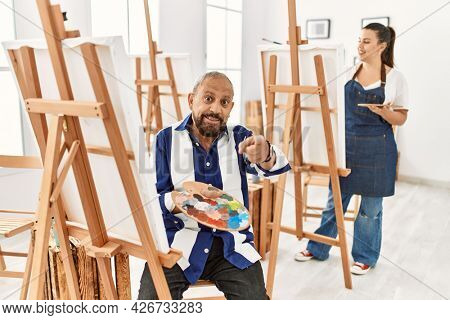 Senior artist man at art studio pointing fingers to camera with happy and funny face. good energy and vibes.