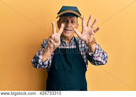 Handsome senior man with grey hair wearing welding protection mask showing and pointing up with fingers number seven while smiling confident and happy.