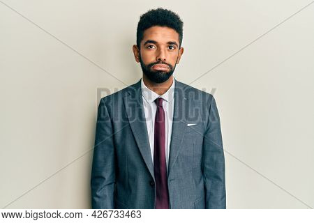 Handsome hispanic man with beard wearing business suit and tie looking sleepy and tired, exhausted for fatigue and hangover, lazy eyes in the morning.