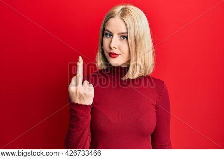 Young blonde woman wearing casual clothes showing middle finger, impolite and rude fuck off expression