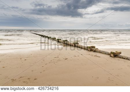 Sewage Or Waste Water Discharge Pipe Leading Out To Sea On A Beach In The Uk