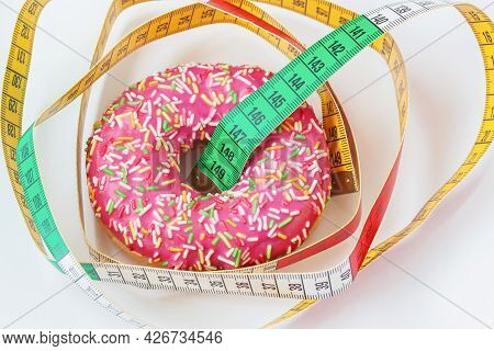 Glazed Donut And Tape Measure Close-up. Concept Of Healthy Food, Dieting, Overweight