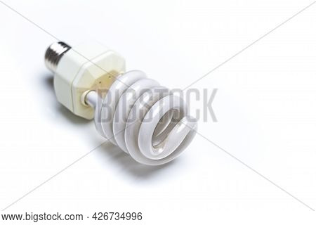 Energy Saving Concepts. Closeup Image Of Used Energy-saving Fluorescent Light Bulb Against White Bac