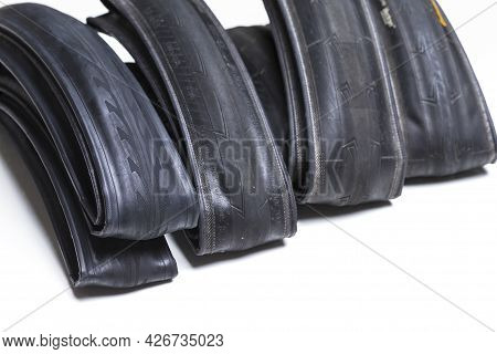 Closeup Image Of Set Of Four Different Road Bike Folded Tyres Placed Together Over White Background.