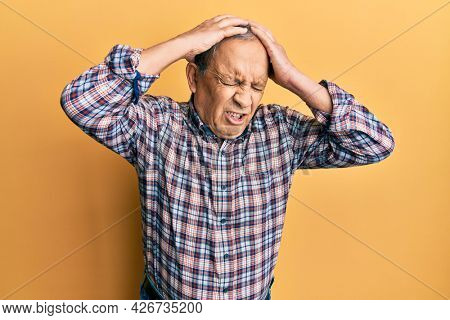 Handsome senior man with grey hair wearing casual shirt suffering from headache desperate and stressed because pain and migraine. hands on head.