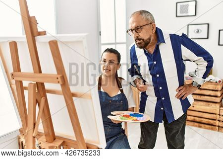 Senior painting teacher man teaching art to young woman painting on canvas at art studio