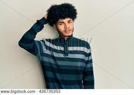 Young african american man with afro hair wearing casual clothes confuse and wonder about question. uncertain with doubt, thinking with hand on head. pensive concept.