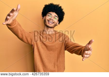 Young african american man with afro hair wearing casual winter sweater looking at the camera smiling with open arms for hug. cheerful expression embracing happiness.
