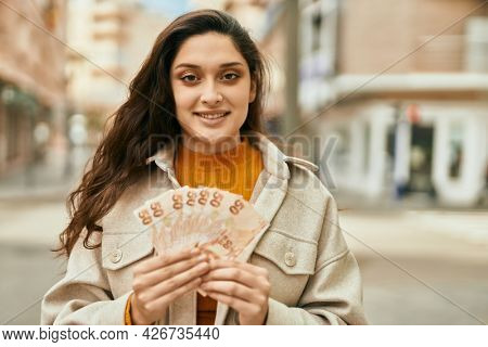 Young middle east woman smiling happy holding turkish lira banknotes at the city.