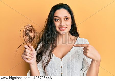Beautiful middle eastern woman holding comb loosing hair pointing finger to one self smiling happy and proud