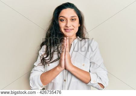 Beautiful middle eastern woman wearing casual clothes praying with hands together asking for forgiveness smiling confident.