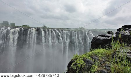 The Majestic Victoria Falls. Powerful Streams Of Water Plunge Into The Abyss. Fog Over The Gorge. In