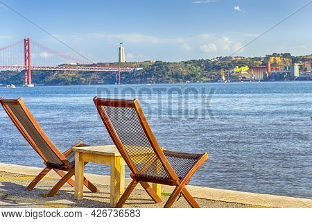 Line Of Wooden Cahris Placed In Front Of 25 April Bridge In Lisbon At Tagus River Shoreline In Lisbo