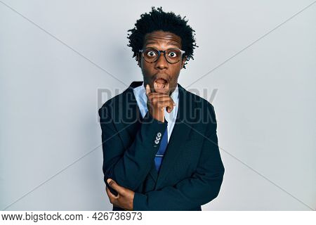Young african american man wearing business suit and tie afraid and shocked with surprise and amazed expression, fear and excited face.
