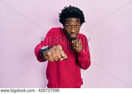 Young african american man wearing casual clothes punching fist to fight, aggressive and angry attack, threat and violence