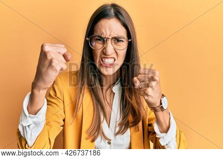 Young beautiful woman wearing business style and glasses angry and mad raising fists frustrated and furious while shouting with anger. rage and aggressive concept.