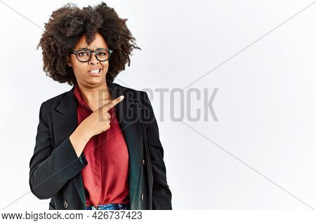 African american woman with afro hair wearing business jacket and glasses pointing aside worried and nervous with forefinger, concerned and surprised expression