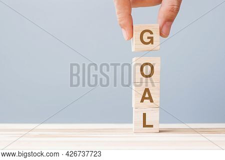 Business Man Hand Holding Wooden Cube Block With Goal Business Word. Target, Aim, Mission, Action An