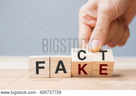 Business Man Hand Holding Wooden Cube With Flip Over Block Fake To Fact. Rumor News, False, Myth, Ev