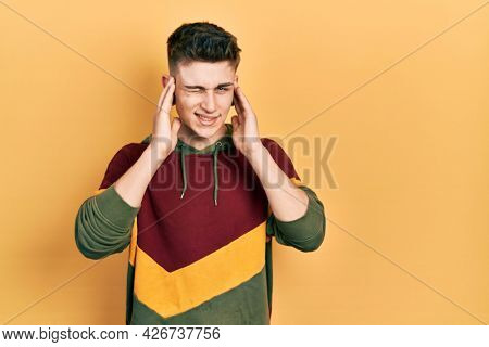 Young caucasian boy with ears dilation wearing casual sweatshirt covering ears with fingers with annoyed expression for the noise of loud music. deaf concept.