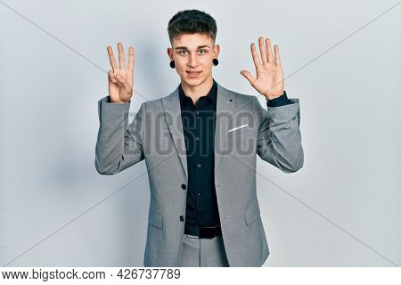 Young caucasian boy with ears dilation wearing business jacket showing and pointing up with fingers number eight while smiling confident and happy.