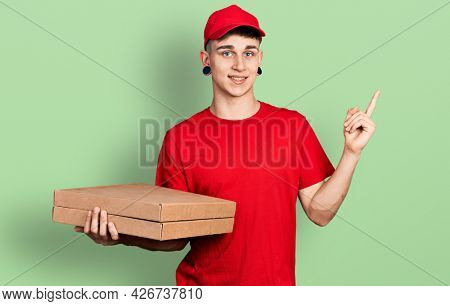 Young caucasian boy with ears dilation holding delivery pizza box smiling happy pointing with hand and finger to the side