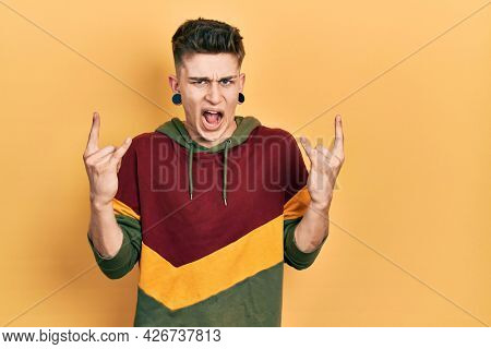 Young caucasian boy with ears dilation wearing casual sweatshirt shouting with crazy expression doing rock symbol with hands up. music star. heavy concept.