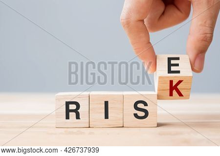 Businessman Hand Flipping Wooden Cube Blocks With Risk Change To Rise Text On Table Background. Econ