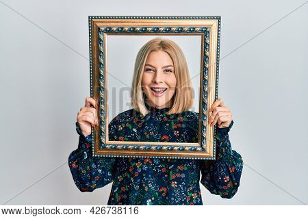 Young blonde woman holding empty frame smiling and laughing hard out loud because funny crazy joke.