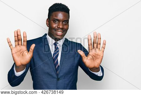Handsome business black man wearing business suit and tie showing and pointing up with fingers number ten while smiling confident and happy.