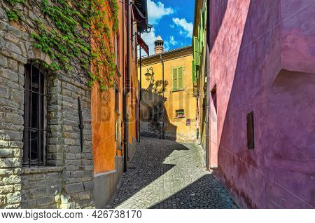 Narrow cobblestone street among old colorful houses in small town of Monforte d'Alba in Piedmont, Northern Italy.
