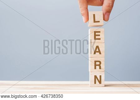 Business Man Hand Holding Wooden Cube Block With Learn Business Word On Table Background. Learning,