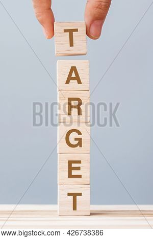 Business Man Hand Holding Wooden Cube Block With Target Business Word. Goal, Aim, Mission, Action An