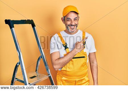Handsome middle age man with grey hair holding ladder cheerful with a smile of face pointing with hand and finger up to the side with happy and natural expression on face