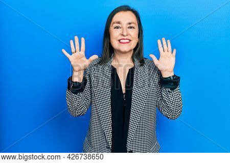 Middle age hispanic woman wearing business clothes showing and pointing up with fingers number ten while smiling confident and happy.