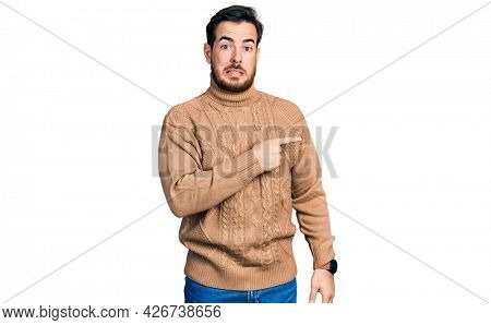 Young hispanic man wearing casual clothes pointing aside worried and nervous with forefinger, concerned and surprised expression