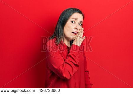 Middle age hispanic woman wearing casual clothes hand on mouth telling secret rumor, whispering malicious talk conversation